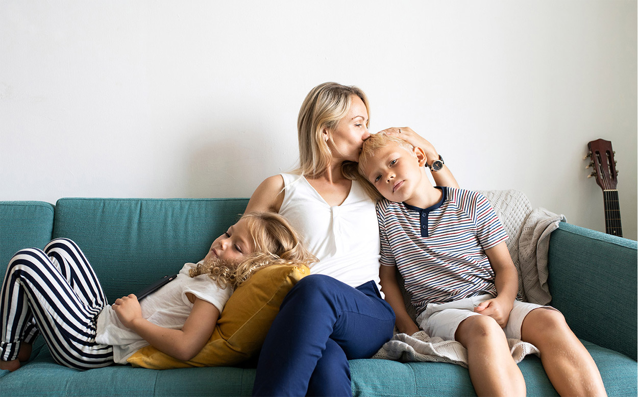 mother sitting on a couch with her children
